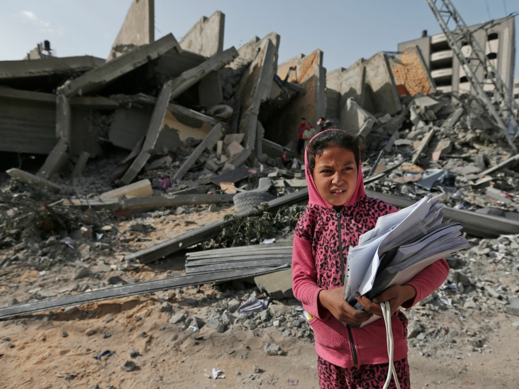 Palestinian leaders in Gaza report that they've agreed to a cease-fire with Israel to end a deadly two-day escalation of violence. Here, a Palestinian girl stands in front of a building on Monday that was destroyed during Israeli airstrikes on Gaza City over the weekend.