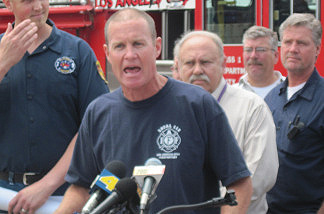 Firefighters and mechanics gather in support as Pat McOsker, the president of the United Firefighters of Los Angeles, speaks at a press conference on May 28, 2010.