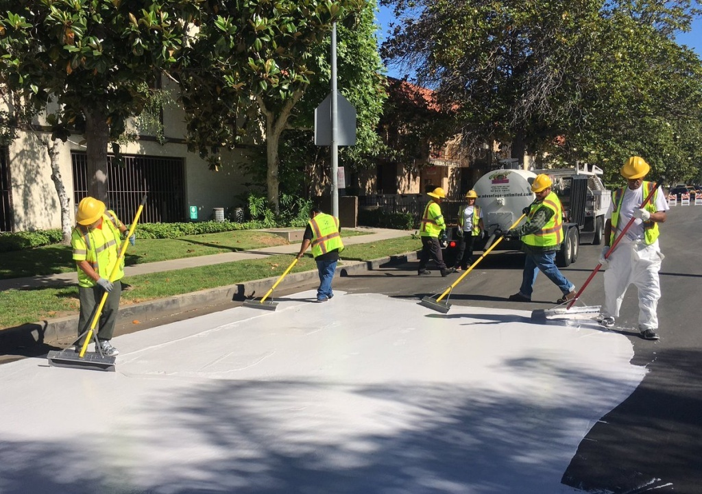 Street crews lay down a new type of reflective seal on a stretch of road in Canoga Park.