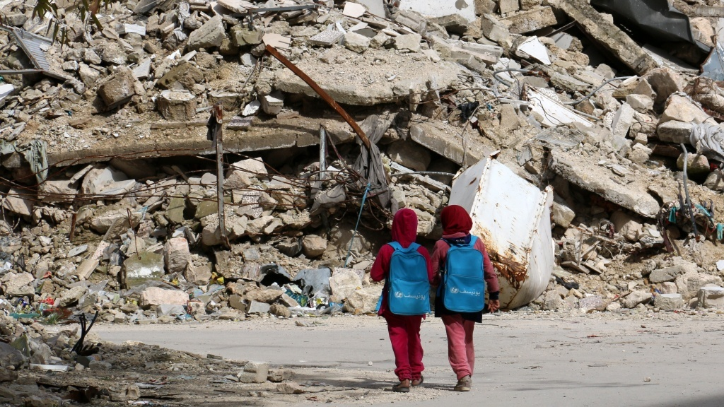 Girls carrying school bags provided by UNICEF walk past destroyed buildings on their way home from school on March 7 in the rebel-held al-Shaar neighborhood of Aleppo, Syria. So many people have fled the city and so much of its infrastructure has been destroyed that nighttime satellite images show 97 percent less light there compared with four years ago.