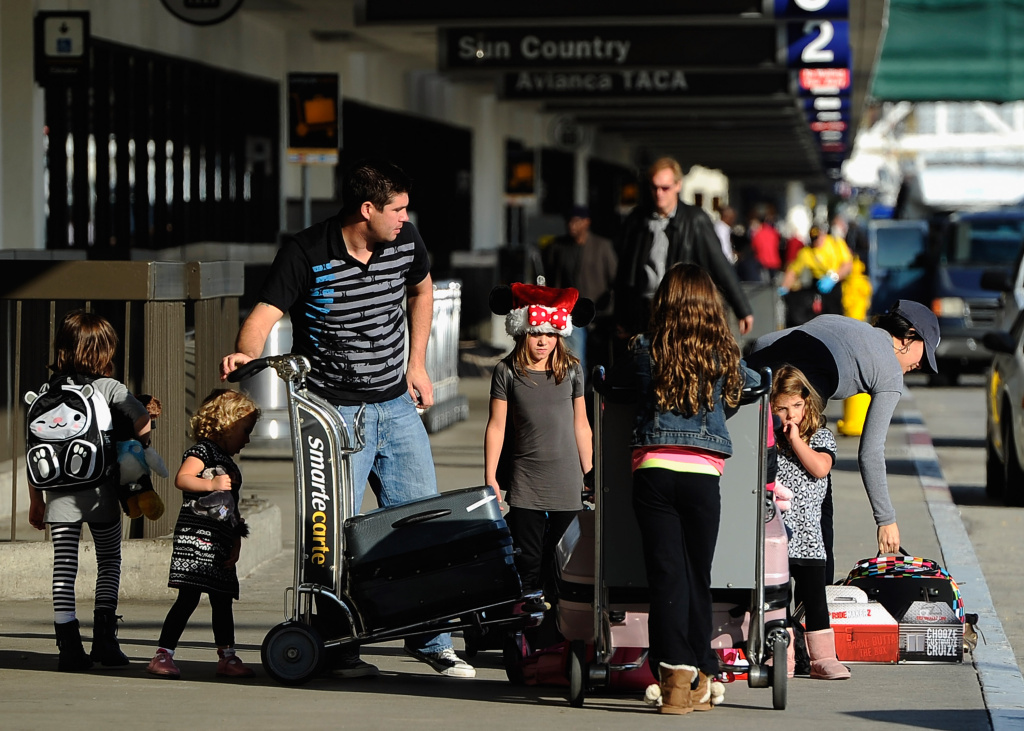 A family stacks luggage on a cart after getting dropped off curbside at the Virgin America terminal at Los Angeles International Airport. The later travelers wait to buy tickets this holiday season, the more those tickets will cost, travel experts say.