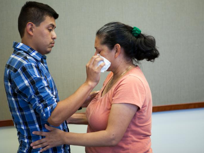 Steven Hernandez wipes a tear from his mother's eye after seeing her for the first time in 20 years in San Bernardino, Calif., on Thursday. Hernandez, 22, was abducted by his father in 1995 when he was 18 months old. Since that time, Maria Mancia, 42, had searched for her son to no avail.