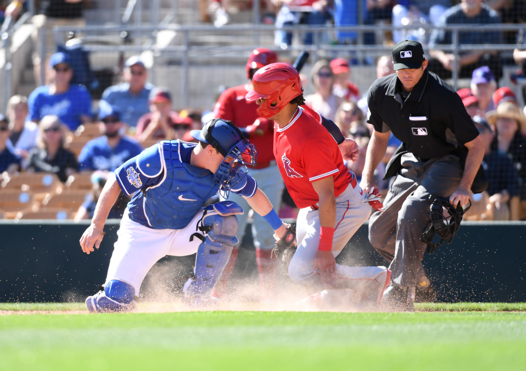 Michael Hermosillo #21 of the Los Angeles Angels is tagged out at home plate by Will Smith #16 of the Los Angeles Dodgers during the fourth inning of a spring training game at Camelback Ranch on February 26, 2020 in Glendale, Arizona.