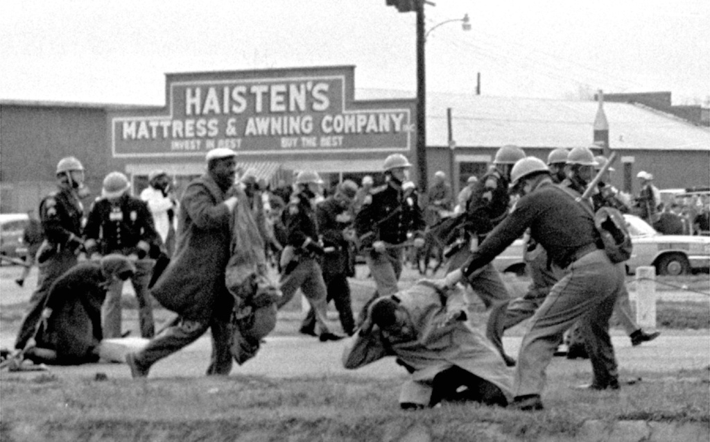 FILE - In this March 7, 1965 file photo, state troopers use clubs against participants of a civil rights voting march in Selma, Ala. At foreground right, John Lewis, chairman of the Student Nonviolent Coordinating Committee, is beaten by a state trooper. The day, which became known as