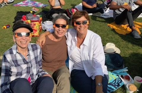 Ellen Isaacs (right) and friends sit on the Griffith Observatory lawn to watch the solar eclipse.