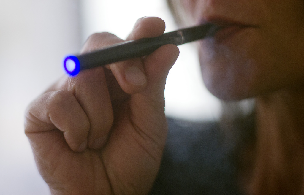 A woman vapes a 'Blu' e-cigarette.
