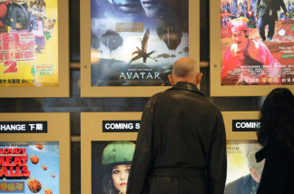 A man stands before posters advertising films including 'Avatar', in Hong kong on December 28, 2009.