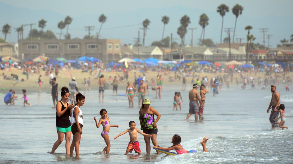 File: Beach goers splash in the Seal Beach waves.