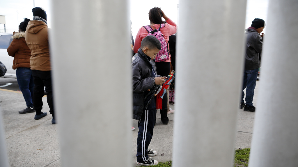A migrant family waits in Tijuana, Mexico, before being transported to the San Ysidro port of entry to begin the process of applying for asylum in the United States. A new Trump administration rule says Central American migrants who pass through a third country en route to the U.S. cannot apply for asylum at the U.S. southern border.