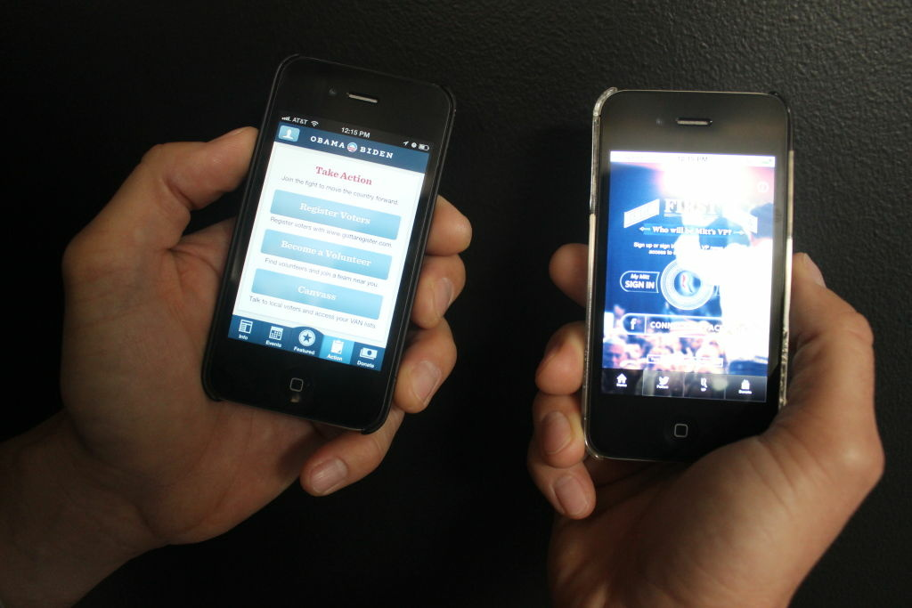 A Patt Morrison producer displays Mitt Romney's and Barack Obama's apps on iPhones.