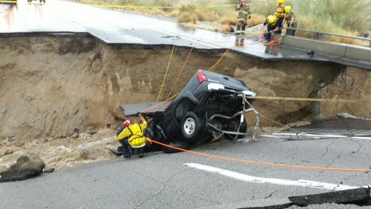 In this photo provided by the CAL FIRE/Riverside County Fire Department, emergency crews respond after a pickup truck crashed into the collapse of an elevated section of Interstate 10, Sunday, July 19, 2015, in Desert Center, Calif. The bridge, which carries the eastbound interstate about 15 feet above a normally dry wash, snapped and ended up in the flooding water below, the California Highway Patrol said, blocking all traffic headed toward Arizona.