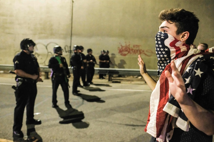 A protester (R) confronts police as protesters shut down the 101 Freeway, a major thoroughfare in the city, following a rally to protest a day after President-elect Donald Trump's election victory in Los Angeles, California, late on November 9, 2016.
