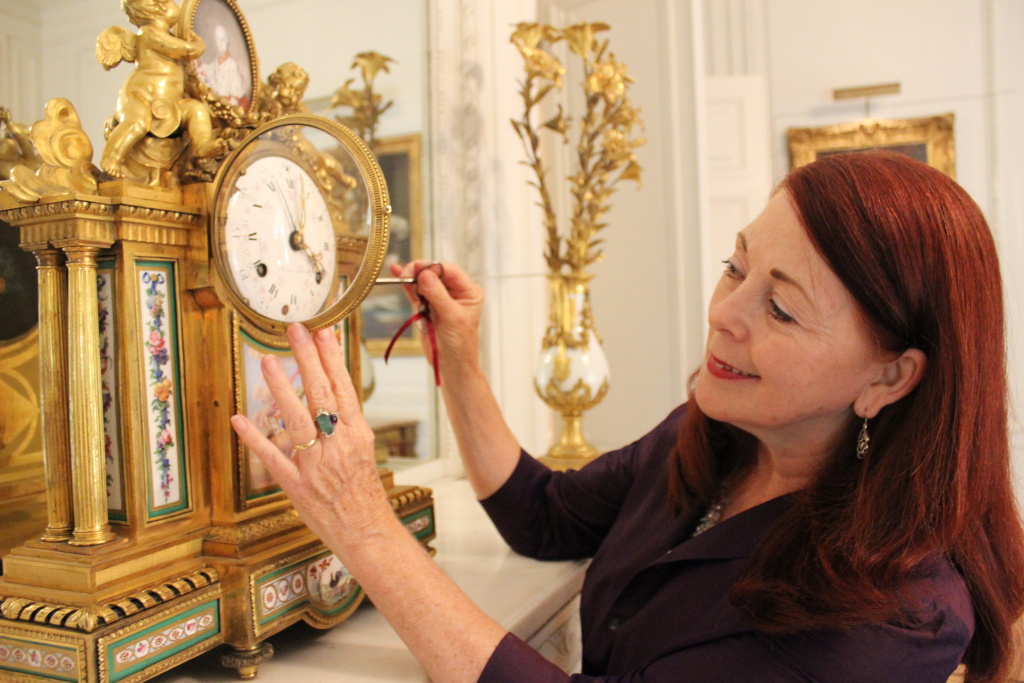 Jacqueline Dugas winds up an 18th century French clock at the Huntington Gallery in San Marino, Calif.