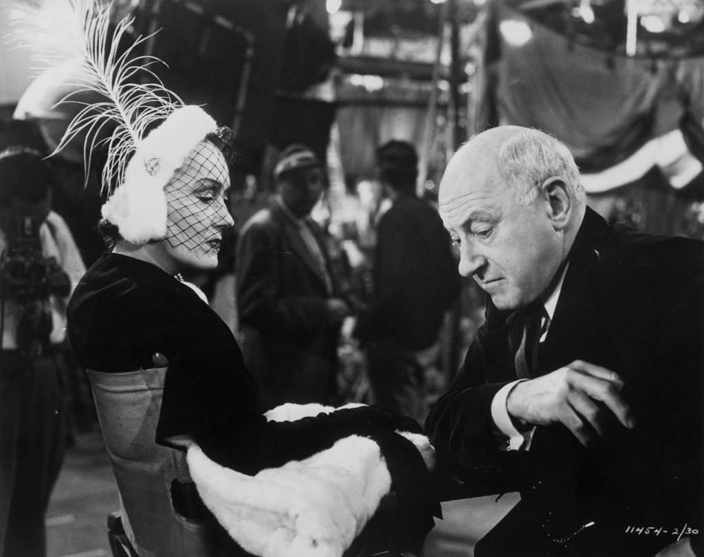 Film actress Gloria Swanson (1897-1983) and film director Cecil B DeMille (1881-1959) sitting together on the set of 'Sunset Boulevard,' a biting satire on Hollywood stardom in which DeMille plays himself, 1949.