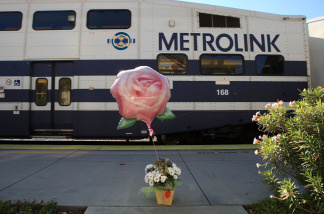 A bouquet of flowers and a balloon stands on the passenger platform as a Metrolink commuter train passes just south of the site of the September 12 head-on collision between a Metrolink commuter train carrying 222 passengers and a freight train, on September 14, 2008.