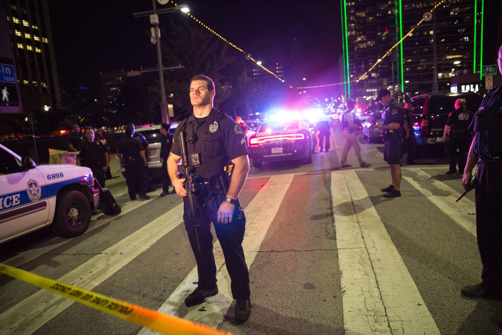 Police officers stand guard at a barricade following the sniper shooting in Dallas.