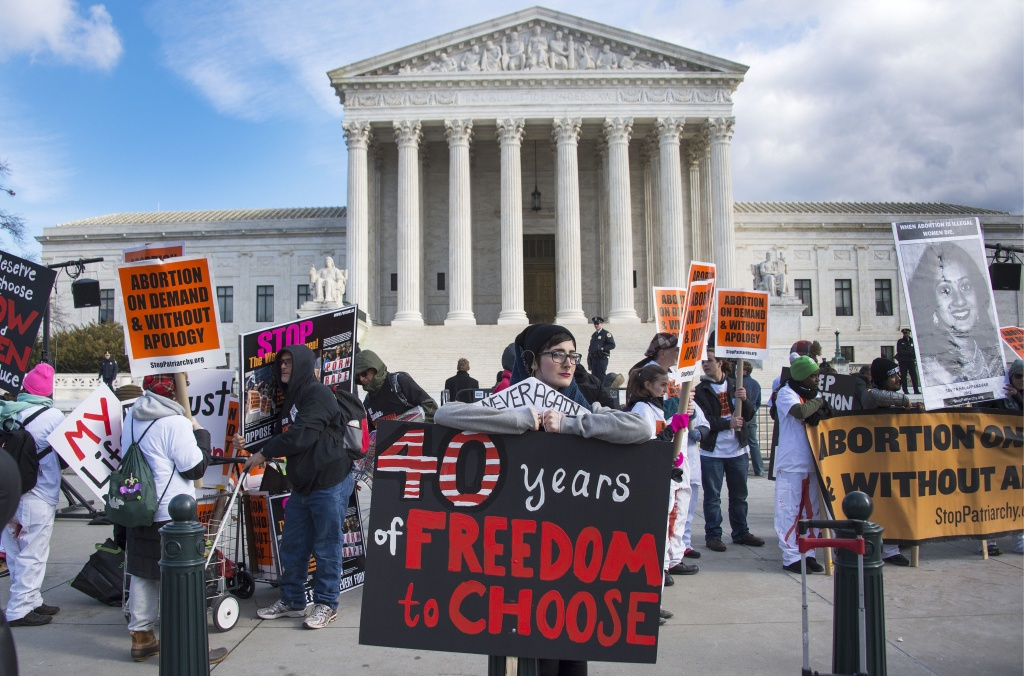 In this file photo, pro-choice activists hold up placards in front of the U.S Supreme Court during the March For Life rally on January 22, 2015. The Supreme Court is taking on its first abortion case in eight years, a dispute over state regulation of abortion clinics.