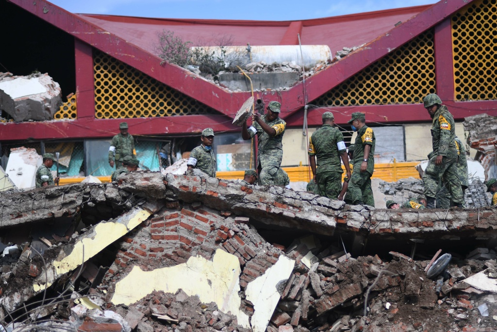 Members of Mexico's armed forces remove debris from collapsed buildings after an 8.1 earthquake hit Mexico's Pacific coast on September 7, 2017 in Juchitan de Zaragoza, Oaxaca.