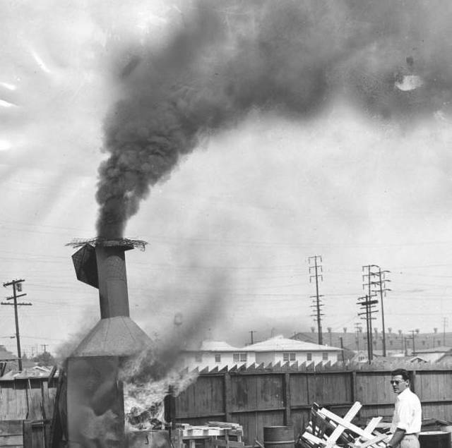 Outdoor view of a residential incinerator burning trash. All refuse burning in Los Angeles will end October 1 when Air Pollution Control District's ban on residential incinerators becomes effective. Photo dated July 1, 1957.