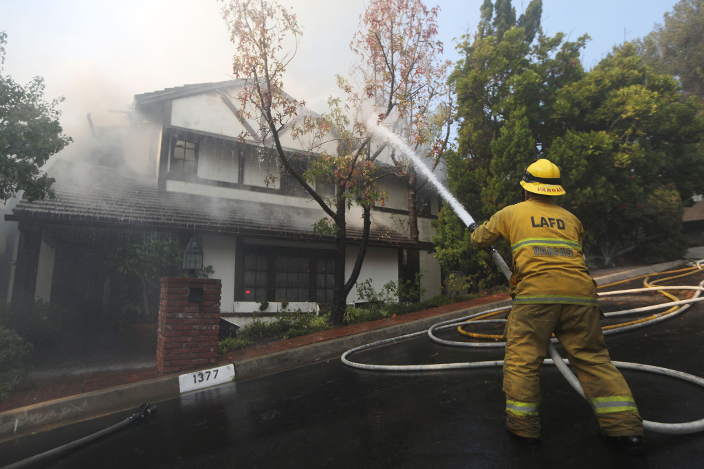 A firefighter sprays water on a burning home in the wealthy Bel-Air neighborhood during the Skirball Fire in this December 6, 2017 file photo.