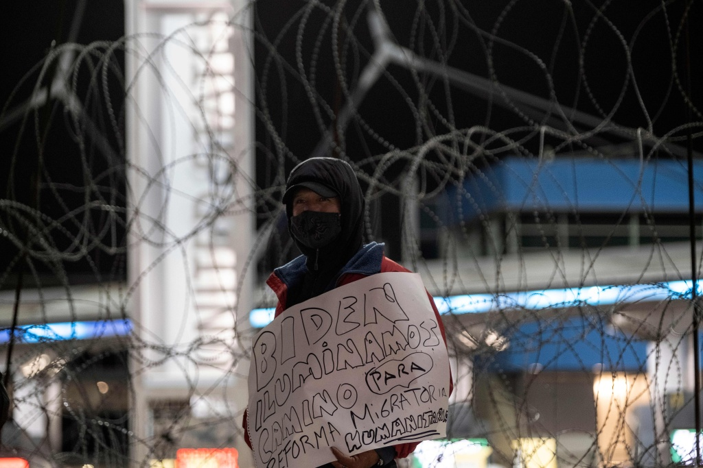 A migrant holds a sign reading