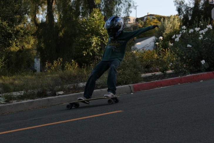 A young boy performs a slide while skateboarding down 14th Street on May 27.