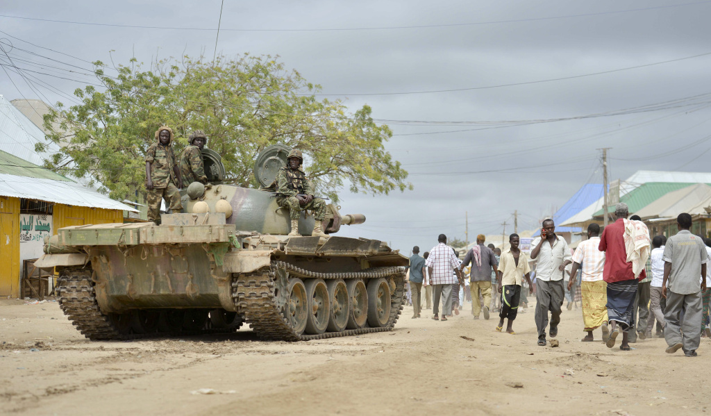 In this photo provided by the African Union Mission to Somalia (AMISOM), African Union (AU) soldiers from Uganda sit on their tank as residents walk past in the town of Bulomarer, in the Lower Shabelle region of Somalia Sunday, Aug. 31, 2014. Somali government and AU troops drove al-Shabab militants from their stronghold of Bulomarer on Saturday as part of their military offensive dubbed