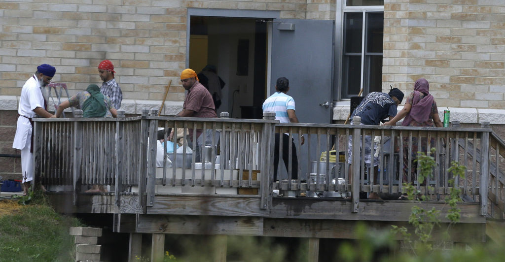 Members of the Sikh temple of Wisconsin wash items as they return for the first time in Oak Creek, Wis.