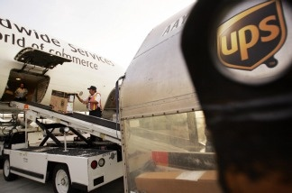 An airport worker helps unload a United Parcel Service (UPS) cargo plane at the company's air hub for Latin America in Miami, Florida.