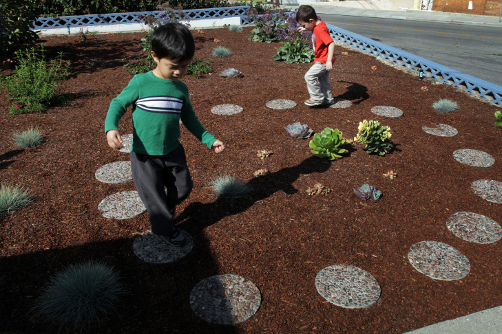 Smart Start Preschool student Kenley Keffeler, 5, examines the wood mulch in her playground. Mulch is used instead of grass to cut back on water usage in Redondo Beach, Calif.