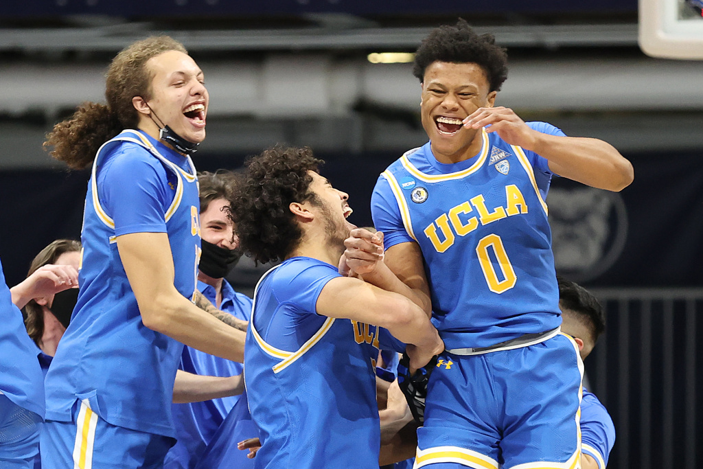 Jaylen Clark of the UCLA Bruins celebrates with Johnny Juzang and Mac Etienne after defeating Alabama in the Sweet Sixteen round game of the 2021 NCAA Men's Basketball Tournament on March 28, 2021 in Indianapolis, Indiana.