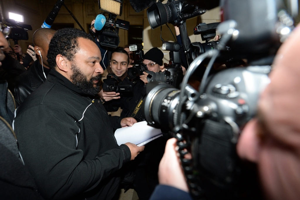 French comedian Dieudonne M'Bala M'Bala arrives for his trial at the courthouse in Paris on Jan. 28. He goes on trial again today on charges of