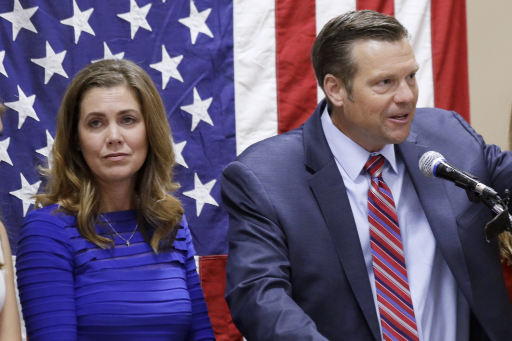 Kris Kobach, right, seen here conceding the Republican primary for U.S. Senate on Aug. 4, 2020 in Leavenworth, Kan. His wife, Heather Kobach, is to his left. Thursday he announced his run for the office of Kansas attorney general.