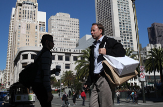 A pedestrian carries shopping bags as he walks through Union Square on Feb. 22, 2011 in San Francisco, Calif. The Conference Board's consumer confidence index reached the highest figure in three years as it rose to 70.4 percent for February, up from 64.8 percent in January.