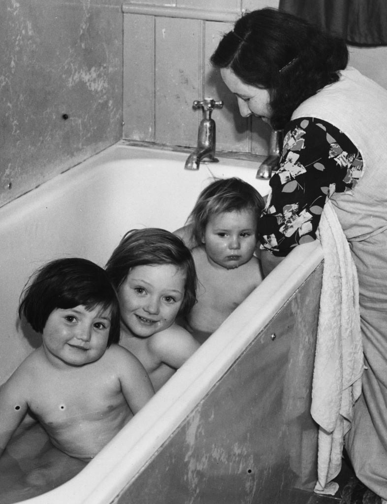 18th December 1940: Evacuated mother Mrs Gwendoline Cook of Mitcham, Surrey, bathes her three children in the bathroom at Stone Hall Mansion, the country house of Lady Denman, chief of the Women's Land Army.