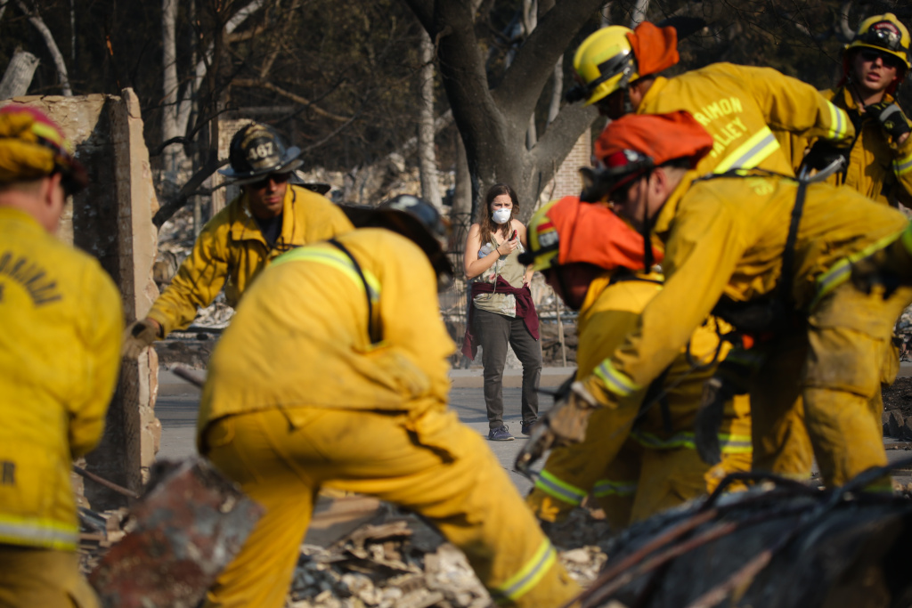 SANTA ROSA, CA - OCTOBER 13: Lisa Corwin, center, watches as firefighters search for a strongbox and a wedding ring through the remains of a neighbor's home in the Fountaingrove neighborhood on October 13, 2017 in Santa Rosa, California. Twenty four people have died in wildfires that have burned tens of thousands of acres and destroyed over 3,500 homes and businesses in several Northern California counties.  (Photo by Elijah Nouvelage/Getty Images)