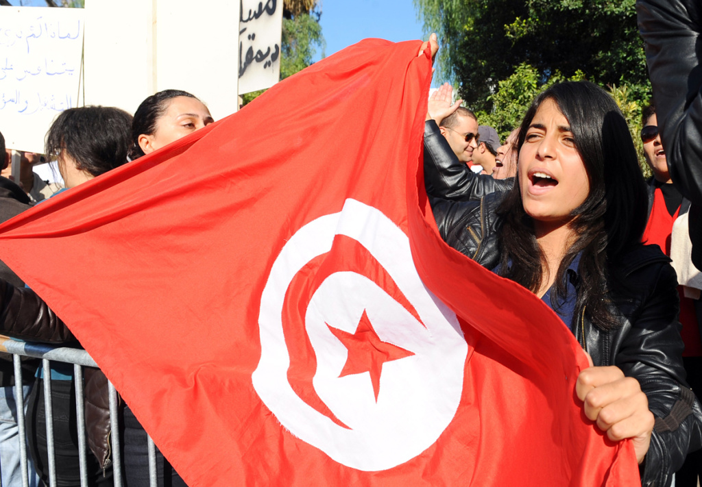 File: A Tunisian woman holds a flag of Tunisia during a demonstration in front of the assembly on December 3, 2011 in Tunis.