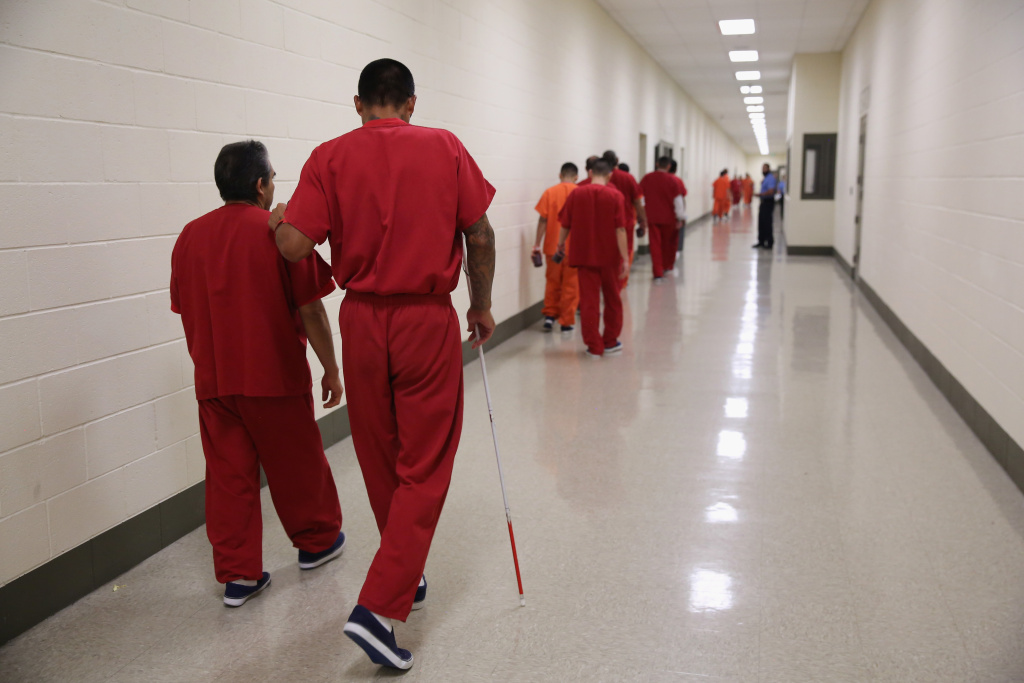 FILE: A blind detainee walks with a fellow immigrant at the Adelanto Detention Facility on November 15, 2013 in Adelanto, California. The facility is the largest U.S. Immigration and Customs Enforcement (ICE) detention center in California.