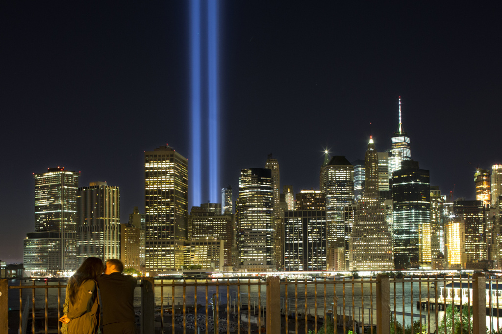 A couple embraces on the Brooklyn Promenade as the Tribute in Light rises above the lower Manhattan skyline Sunday, Sept. 10, 2017, in New York. The two blue pillars of light provide a visual reminder of how the Twin Towers, destroyed in the terrorist attacks of Sept. 11, 2001, once stood above the city skyline. (AP Photo/Mark Lennihan)