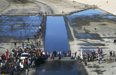 Migrants cross the nearly dry Tijuana River as they make their way around a police blockade toward the El Chaparral port of entry on November 25, 2018 in Tijuana, Mexico. U.S.