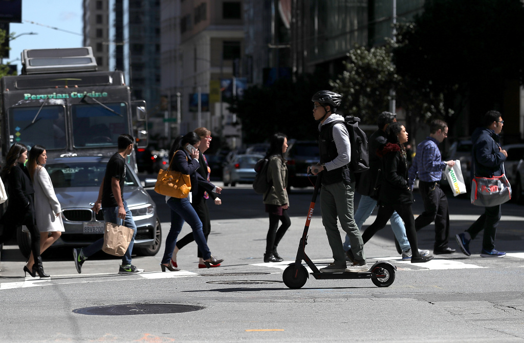 A user rides a Spin scooter on April 17, 2018 in San Francisco.