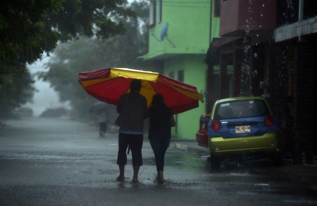 A couple walks in heavy rain before the arrival of hurricane Katia in Tecolutla, Veracruz state, Mexico on September 8, 2017.