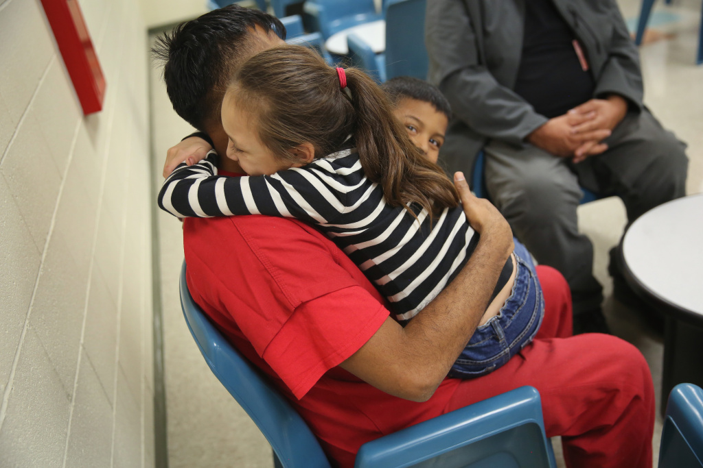 ADELANTO, CA - NOVEMBER 15: An immigrant detainee holds his children during a family visitation visit at the Adelanto Detention Facility on November 15, 2013 in Adelanto, California. The facility, the largest and newest Immigration and Customs Enforcement (ICE), detention center in California, houses an average of 1,100 immigrants in custody pending a decision in their immigration cases or awaiting deportation. The average stay for a detainee is 29 days. The facility is managed by the private GEO Group. ICE detains an average of 33,000 undocumented immigrants in more than 400 facilities nationwide. (Photo by John Moore/Getty Images)