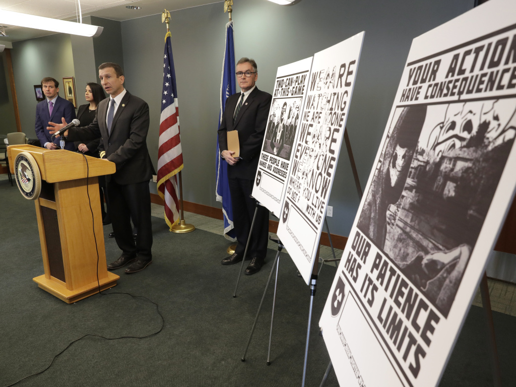 Raymond Duda, FBI Special Agent in Charge in Seattle, speaks in February about charges against a group of alleged members of the neo-Nazi group Atomwaffen Division for cyber-stalking and mailing threatening communications, including the posters at right, in a campaign against journalists in several cities.