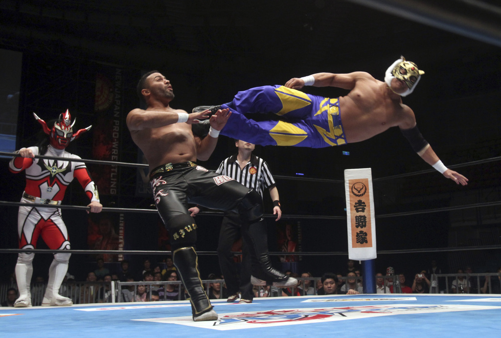 File: Tiger Mask from Japan, right, and Rocky Romero from Cuba compete in a NJPW (New Japan Pro-Wrestling) match in Taipei, Taiwan, Saturday, April 12, 2014.
