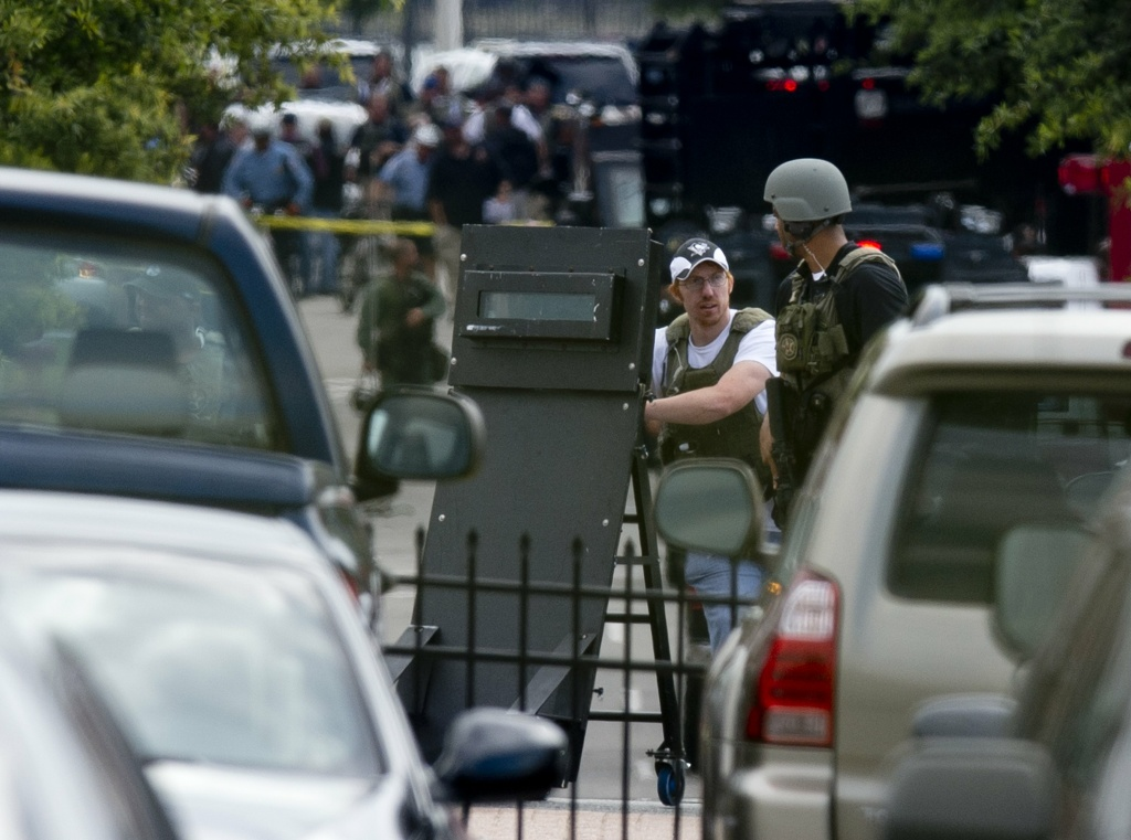 Police tactical units leave after responding to a shooting at the Navy Yard in Washington, DC, September 16, 2013. A shooting rampage at the Washington naval base claimed at least 12 lives including that of an unidentified gunman, city police chief Cathy Lanier told reporters Monday.