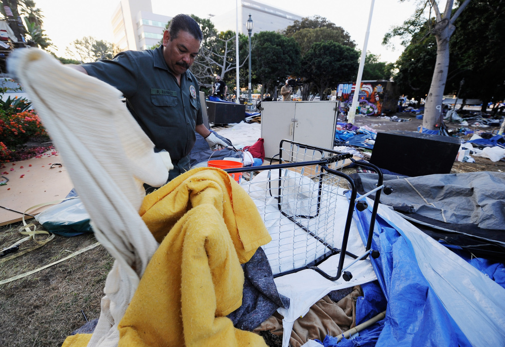 Gino Ramirez, from Los Angeles Sanitation Department, picks up blankets during cleanup of the Occupy Los Angeles encampment.