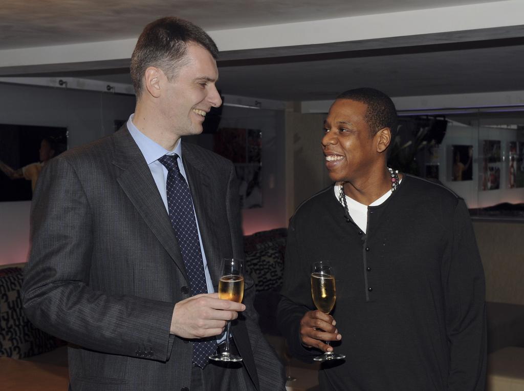 Nets owner Mikhail Prokhorov with Nets investor Jay-Z celebrate Prokhorov's purchase of the team.
