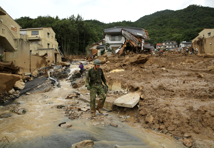 Members of Ground Self-Defense walks in front of the debris of houses destroyed by a landslide caused by torrential rain at the site of a landslide in a residential area on Aug. 20, 2014 in Hiroshima, Japan.