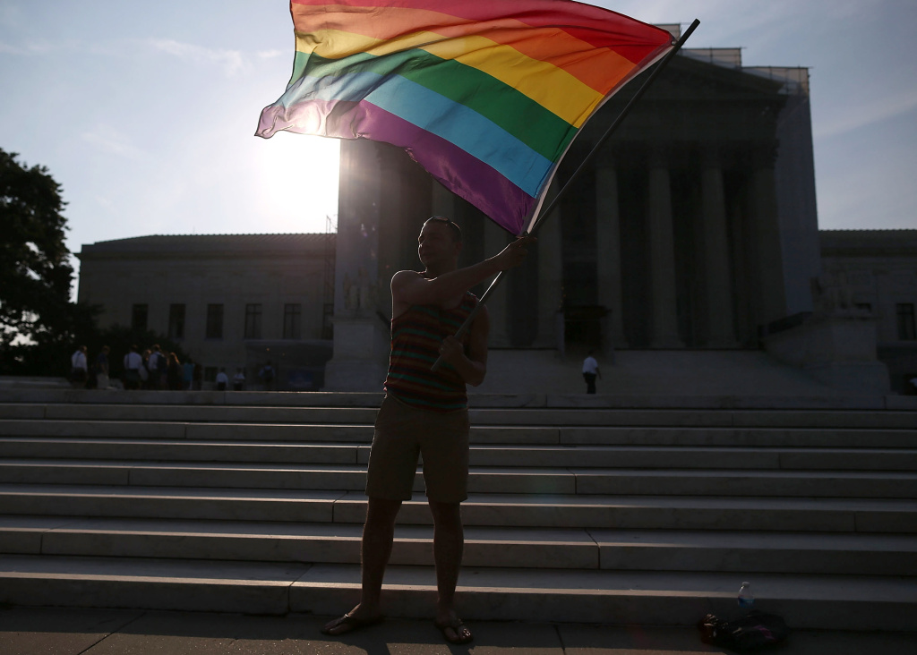 WASHINGTON, DC - JUNE 26:  Gay rights activist Vin Testa of DC, waves a flag  in front of the U.S. Supreme Court building, June 26, 2013 in Washington DC. Today the high court is expected to rule on California's Proposition 8, the controversial ballot initiative that defines marriage as between a man and a woman  (Photo by Mark Wilson/Getty Images)